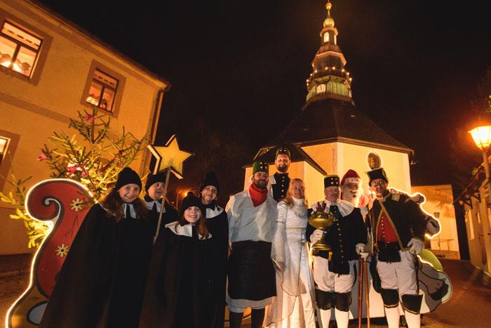 Kurrende, Bergmann und Engel vor der beleuchteten Seiffener Kirche